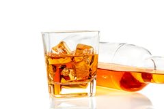 Whiskey near bottle on white background with reflection Stock Photos