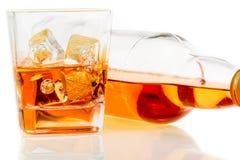 Whiskey near bottle on white background with reflection Stock Image