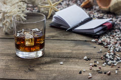 Whiskey and notebook. On the table among the sea rocks Stock Photo