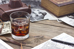 Whiskey and old book. Whiskey on a table next to the old book Royalty Free Stock Photos