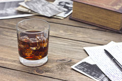 Whiskey and old book. Whiskey on a table next to the old book Royalty Free Stock Images