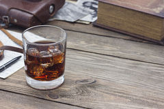 Whiskey with old books. Whiskey with old book on a wooden table Royalty Free Stock Images