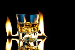 Free Whiskey Or Bourbon In A Transparent Glass With Ice Cubes On A Black Background With Fire Stock Image - 202917701