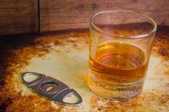 Whiskey ordinato con una taglierina di sigaro rustica sopra immagine stock