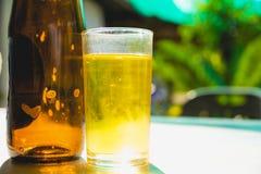 Whiskey ou bière dans un verre et sur une table avec le fond de nature Image stock