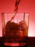 Whiskey over red. Whiskey pour into the glass over red background stock image