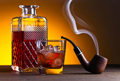 Whiskey and pipe on a wooden table. Whiskey and pipe on a old wooden table Stock Photography