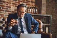 Whiskey potable d'homme d'affaires supérieur fatigué Images stock