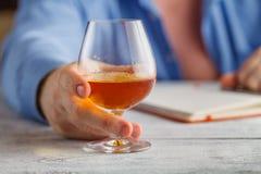 Whiskey potable de jeune homme alcoolique dans sa maison Image stock