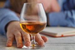 Whiskey potable de jeune homme alcoolique dans sa maison Photographie stock