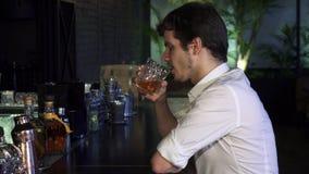 Whiskey potable de jeune homme bel au seul sourire de barre gaiement à l'appareil-photo clips vidéos