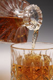 Whiskey Pour. Pouring whiskey from a decanter into a glass tumbler Royalty Free Stock Photos
