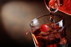 Cocktail Manhattan with cherry. Whiskey is poured from a carafe into a glass with ice.Cocktail Manhattan with cherry.Copy space Stock Photography