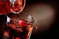 Cocktail Manhattan with cherry. Whiskey is poured from a carafe into a glass with ice.Cocktail Manhattan with cherry.Copy space Royalty Free Stock Image