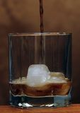 Whiskey poured into a glass. With ice royalty free stock photos