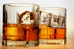 Whiskey on The Rocks. Close-up of liquor and ice in glasses on a white background Stock Photo