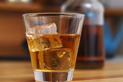 Whiskey on the rocks in glass. Glass of golden burbon whiskey on a table Royalty Free Stock Photo