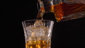 Whiskey on the rocks poured from a rystal decanter stock video footage