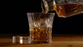 Whiskey on the rocks poured from a rystal decanter stock video
