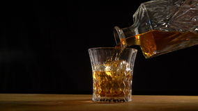 Whiskey on the rocks poured from a rystal decanter stock footage
