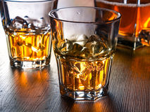 Whiskey on the rocks on a wooden table Stock Images
