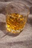 Whiskey on sackcloth Stock Photography