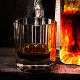Whiskey Scotch glass and a bottle on old wooden background. Old Stock Images
