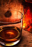 Whiskey Scotch in a glass and a bottle on old wooden table. Old. Vintage oak countertop and glass of hard alcohol.Close up Royalty Free Stock Image