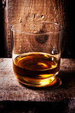 Whiskey Scotch in a glass and a bottle on old wooden table. Old Royalty Free Stock Images