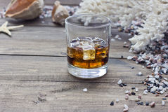 Whiskey among shells. Whiskey among the shells and stones on wooden table Royalty Free Stock Image