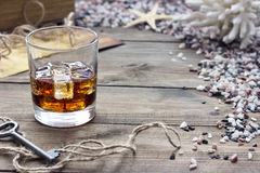 Whiskey among shells. Whiskey on a table among seashells Royalty Free Stock Photos