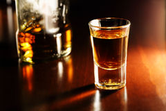 Whiskey shot. And bottle on wooden surface Stock Images