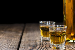 Whiskey Shot. (close-up shot) on rustic wooden background Royalty Free Stock Photo