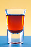 Whiskey in shot glass. On colorful background Royalty Free Stock Photography