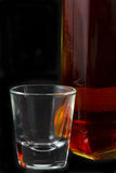 Whiskey and Shot Glass. Whiskey and a shot glass against a black background Royalty Free Stock Photo