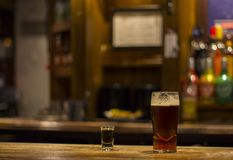 A whiskey shot and a glass of english beer at London pub royalty free stock photography
