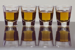 Whiskey Shots. Four shot glasses of whiskey lined up Stock Photos