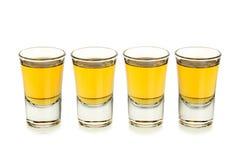 Whiskey shots. Four whiskey shots isolated on white royalty free stock photos