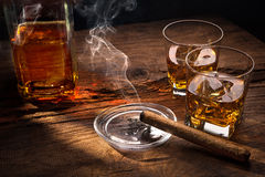 Whiskey with smoking cigar. Glasses of whiskey with smoking cigar on wooden table Stock Photography