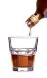 Whiskey som hälls in i ett exponeringsglas Royaltyfri Bild