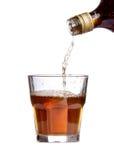 Whiskey som hälls in i ett exponeringsglas Arkivbild