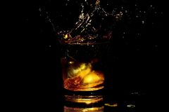 Whiskey splash in a glass. Isolated on a black background Stock Image