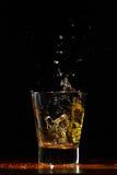 Whiskey splash in glass on black. Whiskey glass on black wood surface Stock Image
