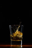 Whiskey splash in glass on black. Whiskey glass on black wood surface Royalty Free Stock Image