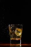 Whiskey splash in glass on black. Whiskey glass on black wood surface Stock Photo