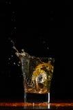 Whiskey splash in glass on black. Whiskey glass on black wood surface Stock Images