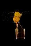 Whiskey splash with two lemons black background. A glass of Whiskey splash with two lemons against black background Royalty Free Stock Image
