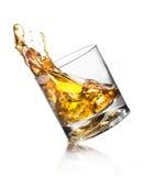 Whiskey. Splashing of whiskey out of glass isolated on white Stock Photos