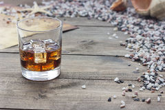 Whiskey stones near the sea. On the table Stock Photography