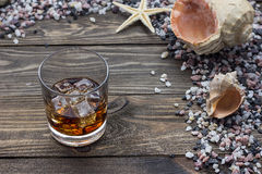 Whiskey on the table. Whiskey on a table among seashells and stones Stock Photo